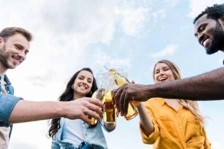 Photo for Low angle view of cheerful multicultural men and women clinking bottles with beer - Royalty Free Image