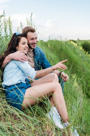 Photo for Selective focus of cheerful young woman sitting with handsome man on green grass and pointing with finger - Royalty Free Image