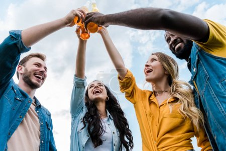 Photo for Bottom view of cheerful multicultural women and men clinking bottles with beer - Royalty Free Image