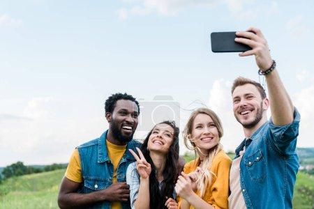 Photo pour Selective focus of happy friends taking selfie against blue sky with clouds - image libre de droit