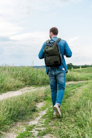 Photo for Back view of young man walking with backpack on green grass - Royalty Free Image