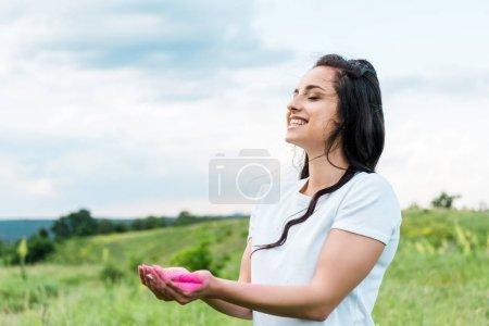 Photo pour Jeune femme heureux restant et retenant la poudre rose dans des mains - image libre de droit