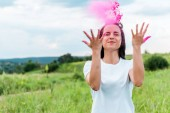 "Постер, картина, фотообои ""happy young woman standing with closed eyes and throwing in air pink powder """