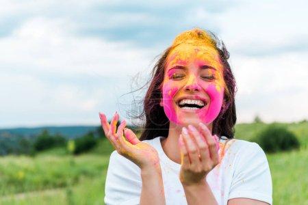 Foto de Mujer feliz de pie con los ojos cerrados y pintura holi rosa y amarillo en la cara - Imagen libre de derechos