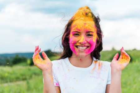 Photo pour Femme heureuse avec la peinture rose et jaune de holi sur le visage - image libre de droit