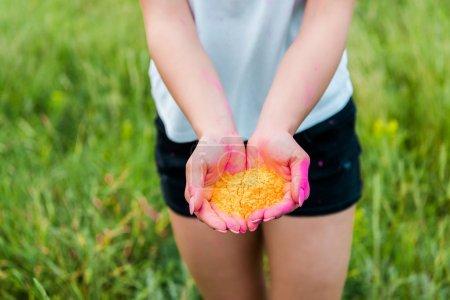 Foto de Enfoque selectivo de la mujer joven sosteniendo pintura holi amarilla en las manos - Imagen libre de derechos