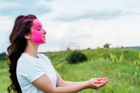 happy woman with pink holi paint on face standing with cupped hands