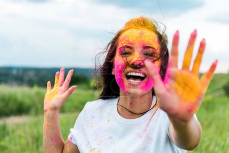 selective focus of happy woman with pink and yellow holi paint on face and hands