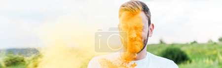 Photo for Panoramic shot of young man with closed eyes near splash of yellow holi paint - Royalty Free Image