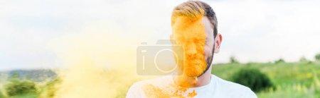 Photo pour Tir panoramique de jeune homme avec les yeux fermés près de l'éclaboussure de peinture holi jaune - image libre de droit