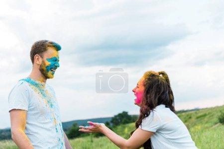 Foto de Happy man and woman with holi paint on faces giving high five - Imagen libre de derechos