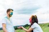 """Постер, картина, фотообои """"счастливый мужчина и женщина с холи краски на лицах дает высокие пять"""""""