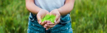 Photo pour Tir panoramique de jeune femme retenant la peinture verte holi dans les mains - image libre de droit