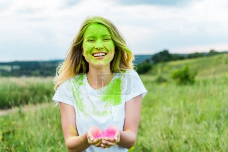 Photo for Cheerful woman with green holi paint on face standing with cupped hands and smiling outdoors - Royalty Free Image