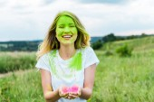 "Постер, картина, фотообои ""cheerful woman with green holi paint on face standing with cupped hands and smiling outdoors """