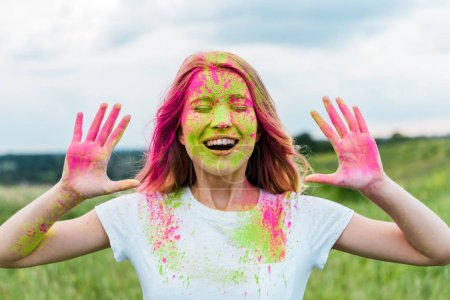 Foto de Cheerful woman with closed eyes and pink holi paint on hands gesturing and smiling outdoors - Imagen libre de derechos