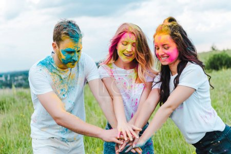 Photo for Cheerful group of friends with holi paints on faces putting hands together - Royalty Free Image