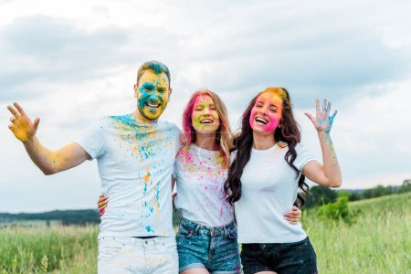 Photo for Happy group of friends with holi paints on faces smiling outdoors - Royalty Free Image