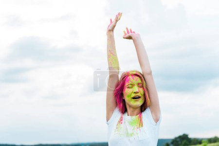 Photo for Young woman with closed eyes, green and pink holi paint on outstretched hands - Royalty Free Image
