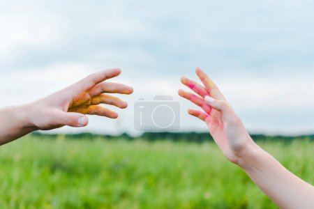 Photo for Cropped view of man and woman with holi paint on hands gesturing near blue sky - Royalty Free Image