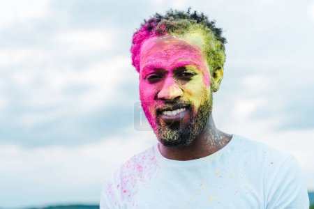 Photo for Handsome african american man in white t-shirt and colorful holi paints on face - Royalty Free Image
