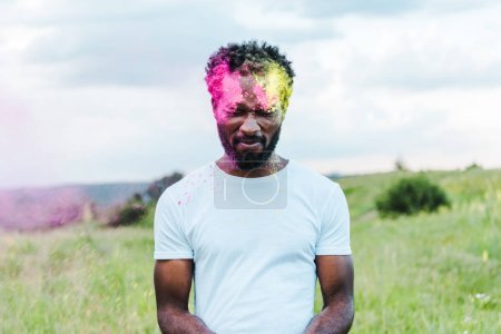 Foto de African american man with closed eyes in white t-shirt and colorful holi paints on face - Imagen libre de derechos