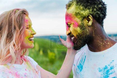 glückliche Frau berührt Gesicht eines afrikanisch-amerikanischen Mannes mit Holi-Farbe im Gesicht