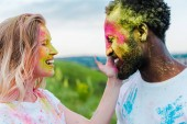 happy woman touching face of african american man with holi paint on face