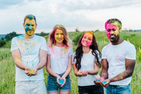 Photo for Happy multicultural friends holding colorful holi paints in hands - Royalty Free Image