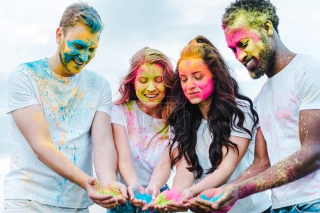 Photo for Happy girls near multicultural men holding holi paints - Royalty Free Image