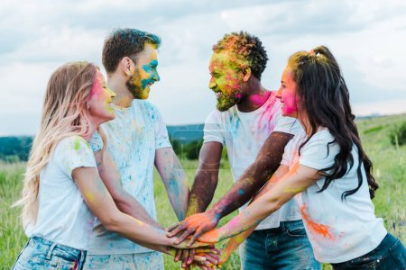 Photo pour Happy girls and multicultural men with colorful holi paints on faces putting hands together - image libre de droit