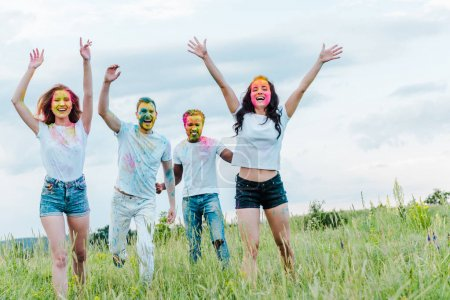 happy multicultural friends with colorful holi paints on faces gesturing while standing outside