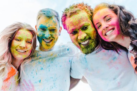 Photo for Bottom view of happy multicultural friends with colorful holi paints on faces - Royalty Free Image