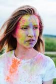 """Постер, картина, фотообои """"привлекательная молодая женщина с холи краски на лице"""""""