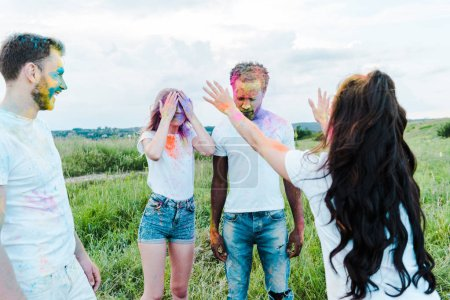 Photo for Back view of woman throwing in air holi paints near multicultural friends - Royalty Free Image