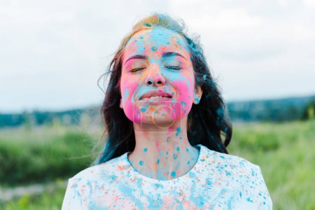 Photo for Positive woman with closed eyes and colorful holi paints on face - Royalty Free Image