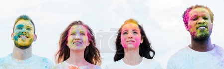 Photo for Panoramic shot of handsome african american man and cheerful friends with holi paints on faces - Royalty Free Image