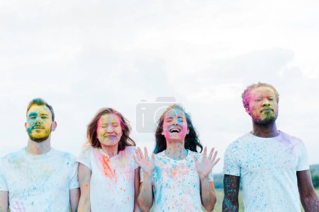 Photo for Handsome african american man and cheerful friends with holi paints on faces and closed eyes - Royalty Free Image