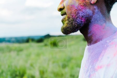 Photo for Cropped view of cheerful african american man with colorful holi paints on face - Royalty Free Image