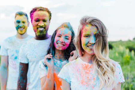 Photo for Selective focus of happy woman near multicultural friends with holi paints on faces - Royalty Free Image