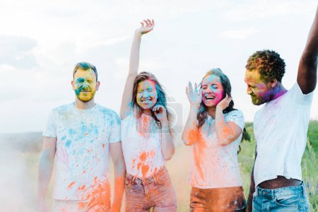 Photo for Happy woman gesturing near multicultural friends with holi paints on faces - Royalty Free Image