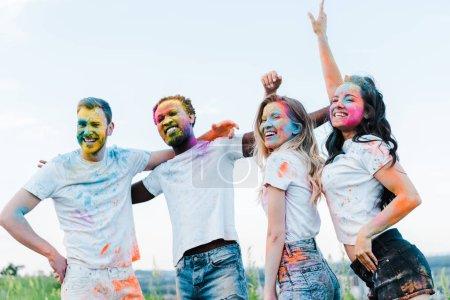 Photo pour Happy man with hand on hip near multicultural friends with holi paints on faces - image libre de droit