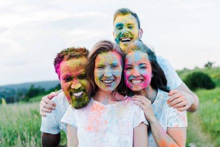 Photo pour Selective focus of multicultural friends with holi paints on faces smiling near man - image libre de droit