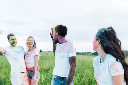 Photo for Selective focus of multicultural friends with holi paints on faces waving hands - Royalty Free Image