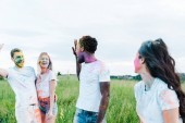 """Постер, картина, фотообои """"selective focus of multicultural friends with holi paints on faces waving hands """""""