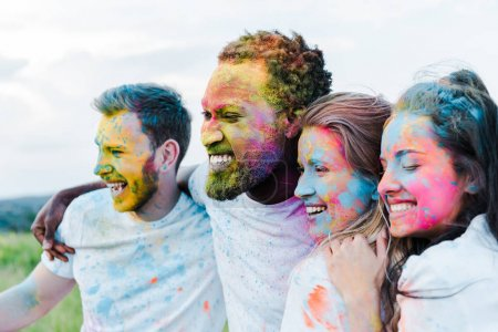 selective focus of happy african american man near friends with holi paints on faces