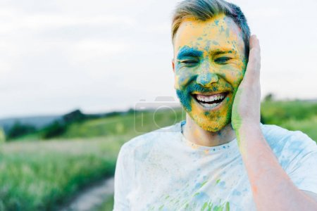 Photo for Happy young man with yellow and blue holi paints on face - Royalty Free Image