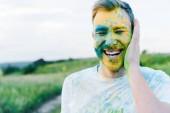 """Постер, картина, фотообои """"счастливый молодой человек с желтыми и синими красками Холи на лице"""""""