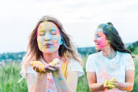 Photo pour Foyer sélectif de la femme avec les yeux fermés soufflant la poudre colorée près de la fille - image libre de droit