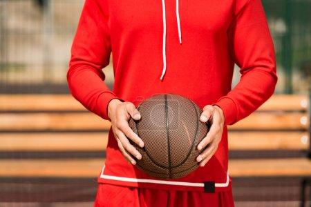 Photo pour Vue partielle du joueur de basket-ball retenant la bille près du banc en bois - image libre de droit